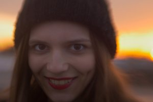 Portrait of beautiful young woman with red lips at sunset