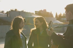 Two girls smiling while guy playing on the guitar at the sunset outdoors