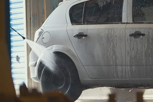 Worker with the water hose in car-washing facility