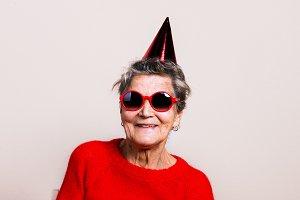 Portrait of a senior woman in studio. Party concept.