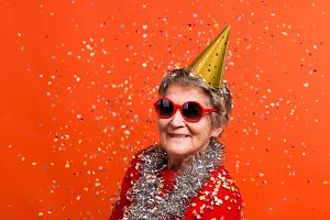 Portrait of a senior woman in studio on a red background. Party concept.