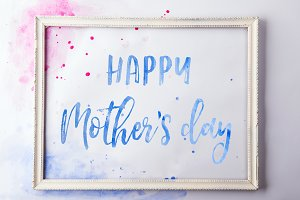 Happy mothers day composition. A text in a wooden frame on white background. Studio shot.
