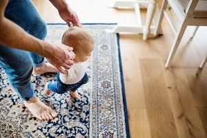Father with a baby girl at home. First steps.