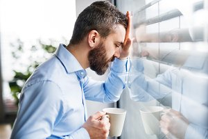 An unhappy man by the window holding a cup of coffee.