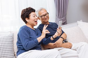 Senior Asian couple grandparents making a video call and waving at the caller