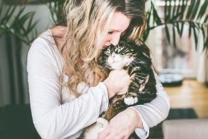 Women cuddle with cat