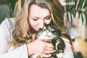 Woman holds and kisses funny cat