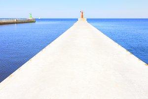 A pier in the sea with an alarm beacon