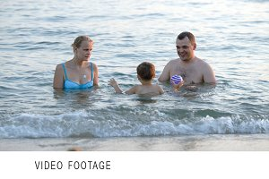 Parents and son playing ball in sea