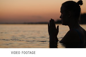 Woman in water praying or meditating