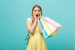Lifestyle Concept: Portrait shocked young brunette woman in yellow summer dress posing with shopping bags isolated over pastel blue background