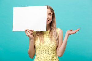 Lifestyle Concept: young beautiful girl smiling and holding a blank sheet of paper, dressed in yellow, isolated on pastel blue background