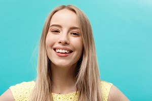 Portrait and Lifestyle Concept: Happy cheerful young woman wearing yellow dress looking at camera with joyful and charming smile.