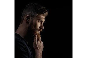 Attractive pensive young man looks into the distance stroking his beard