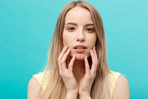 Beauty Concept: Portrait of beauty model with natural nude make up and touching her face. Spa, skincare and wellness. Close up, blue background, copyspace.