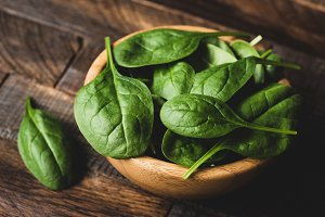 Baby spinach leaves in wooden bowl