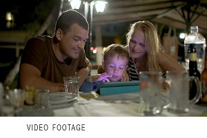 Family with tablet PC outdoor cafe