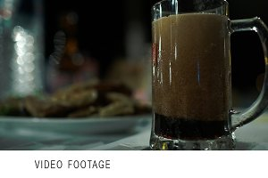 Pouring dark beer into glass mug