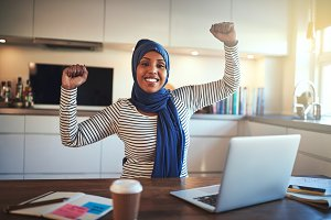 Young Arabic woman excitedly celebrating her business success at home