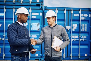 Engineers shaking hands together in a commercial freight yard