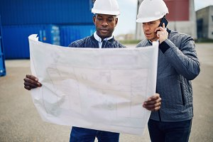 Engineers discussing building plans while standing in a shipping yard