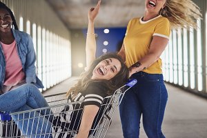 Laughing female friends pushing each other in a shopping cart