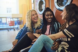 Young friends laughing together on the floor of a laundromat