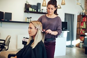 Young hairdresser straightening a clients hair in her salon