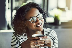 Smiling young African woman drinking coffee in a cafe