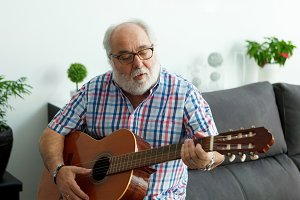 Senior man at home playing guitar
