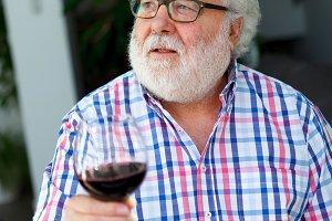 Senior man at home drinking wine