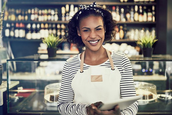 People Stock Photos: Stefan & Janni - Smiling African hostess standing in her cafe using a tablet