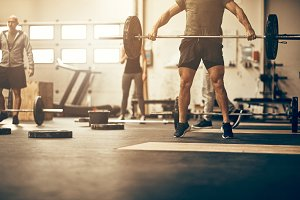 Fit people working out with weights together at the gym