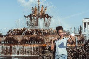 Black girl taking selfie, fountain