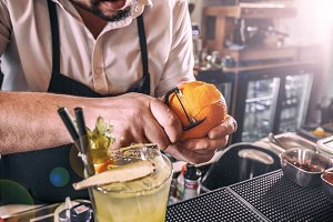 Bartender peeling an orange