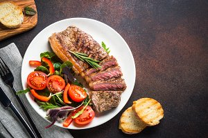 Grilled beef striploin steak with fresh salad top view.