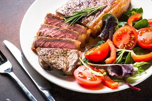 Grilled beef striploin steak with salad in plate.