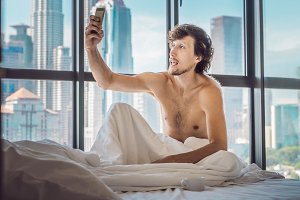 Man wakes up in the morning in an apartment in the downtown area with a view of the skyscrapers and uses smartphone. Life in the noise of the big city concept. Not enough sleep