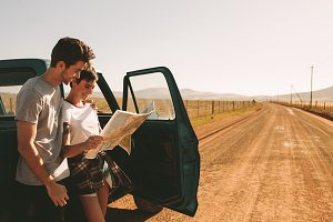 Couple on a road trip looking at map
