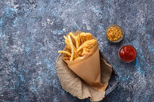 Fish and chips with tomato sauce and mustard
