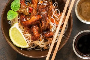 Asian dish glass noodles with vegetables and meat. Pork fried with sweet sour sauce. Stir-Fred
