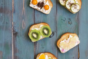 Sandwiches with cream cheese and fresh fruit on a green rustic wooden background, vertical frame. Top view, space for text.