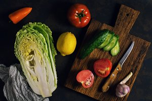 Fresh raw vegetables on a rustic background - Peking cabbage, pepper, tomato, cucumber, lemon, garlic. The concept of healthy eating. Vegetarian food, top view