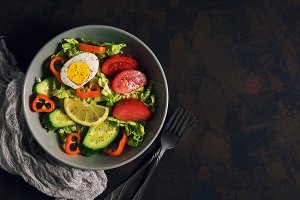 A diet vegetarian salad of fresh vegetables is served in a gray plate on a dark rustic background. Top view, copy space.