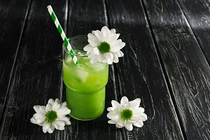 A green cocktail with striped straws is decorated with white flowers. Kiwi juice with ice on a wooden black table. Place for your text.