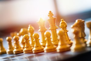 gold chess pieces on a chessboard