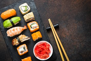 Sushi and sushi roll set on stone table top view