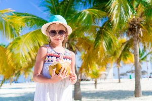 Little happy girl with big coconut on the beach