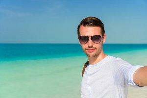 Happy man taking selfie on tropical beach