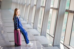 Adorable little girl in airport near big window